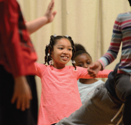 Girl smiling as she is performing in a culminating event at PS 112 Bronx