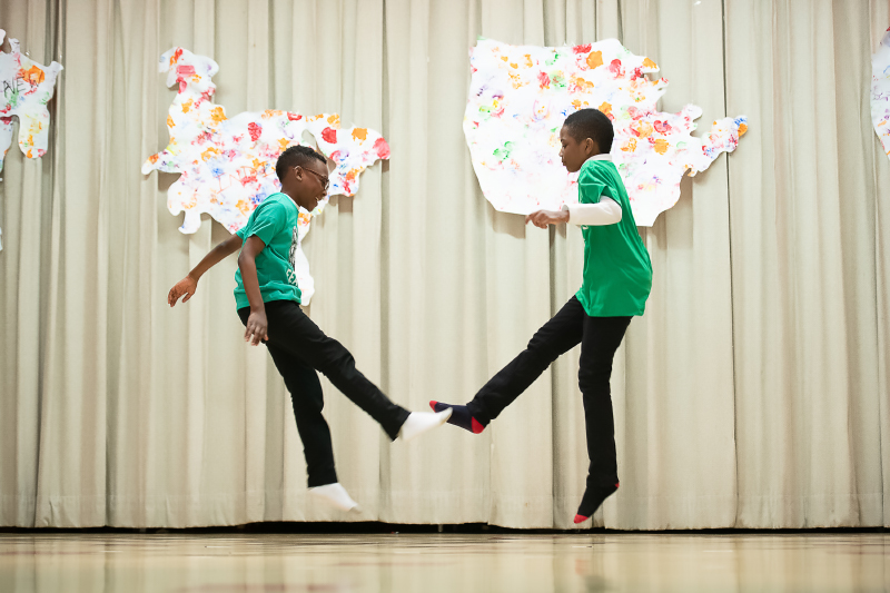 two students doing the kid and play in the air