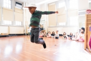 Young boy in PreK leaping for joy